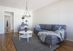 Foto. Ett vardagsrum med grå soffa, grå matta och vitt soffbord. I taket hänger en ljuskrona.