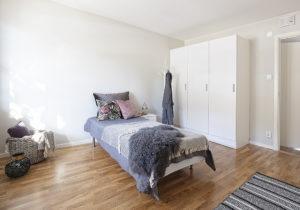 Foto. Ett vitt sovrum. En enkelsäng och tre garderober finns i rummet.
